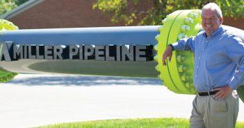 Doug Banning in front of Miller Pipeline sign